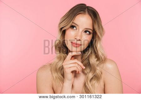 Portrait of a smiling beautiful young girl with blonde curly hair standing isolated over pink background, posing, touching face