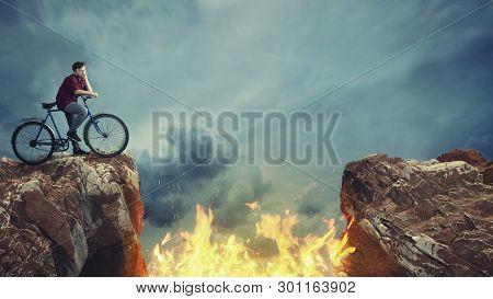 Thughtful Man On Bike Standing On Mountain Peak. Fire Between A Gap Of Two Mountain Peaks.
