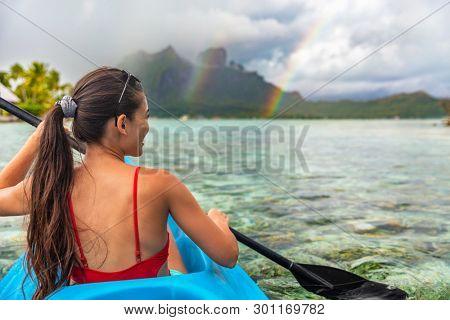 Kayak woman watersport activity tourist enjoying kayaking in Bora Bora at Mount Otemanu, Tahiti, French Polynesia. Active ocean sport lifestyle.