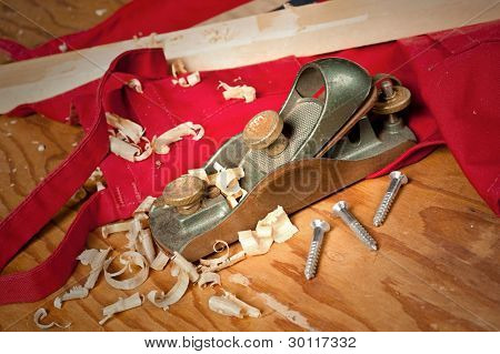 An old wood planer with curled shavings on a red workshop apron for use as a woodcraft inference.