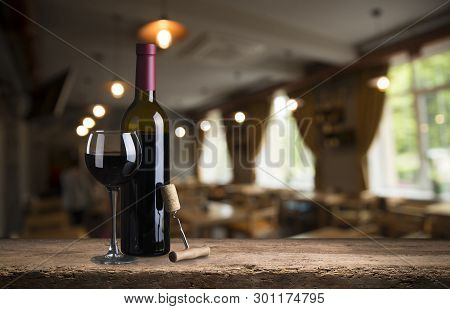 Red Wine Tasting In The Wine Cellar: Wineglass And Bottles Next To The Window And Panoramic View Of