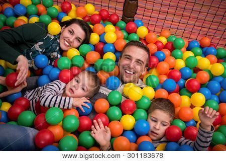 happy family enjoying free time young parents and kids playing in the pool with colorful balls at childrens playroom