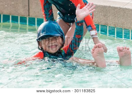 Asian Siblings Is Swimming And Chasing In Swimming Pool