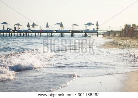 White Wave On The Sandy Beach. The Shore Of The Blue Sea Against The Pier. Pier By The Sea In Turkey