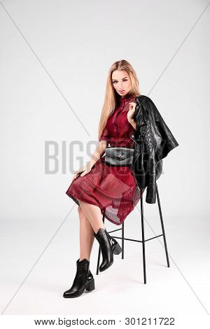 Young stylish woman in trendy shoes with bum bag sitting on bar stool, light background poster