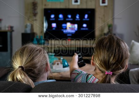 Two Children Sliding Through The Apps On A Smart Tv. Back Of The Children With The Focus On The Chil