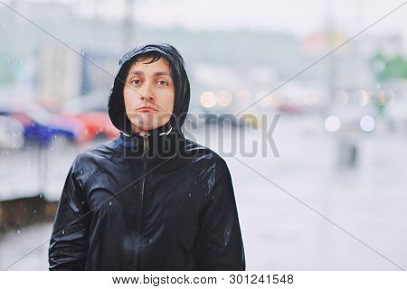 Wet Young Man In Raincoat With Unhappy Face Walks Along The Street During Heavy Rain, Close-up. Autu