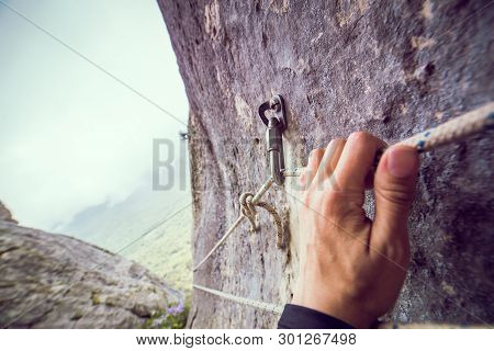 Worn Out And Damaged Rapid Carbine With Rope For Rappeling In The Rock  In Mountains. Hand Holds The