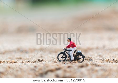 Miniature People : Travellers Riding A Bicycle , Exploring The World Concept