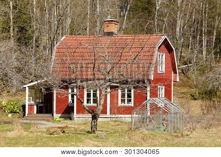 Typical Swedish Countryside Old Wooden Single-family Red Dwelling With A Mansard Roof.