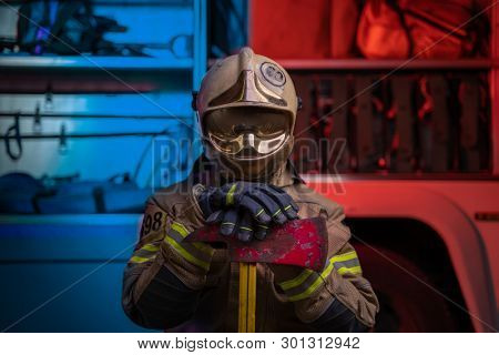 Photo of man fireman in helmet and helmet with pick on background of fire truck