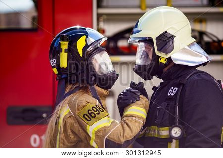 Photos of firefighters women and men in helmet and mask looking at each other and doing handshake near fire truck
