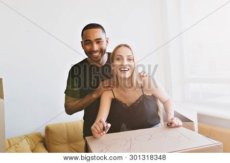 Happy Couple Moving To New Home, Relocating To Apartment, Flat. Cheerful Man And Woman Packing Boxes