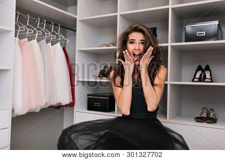 Enthusiastic Young Woman Stands In The Closet And Jumps. Her Dress Hovers In The Air, She Looks Into