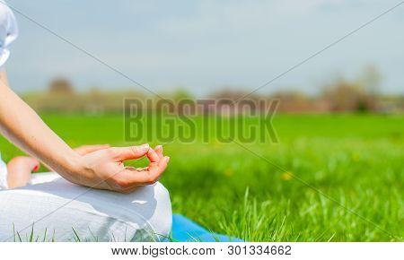 Meditation. Woman Is Meditating Sitting In Lotus Pose On Grass At The Park. Girl Doing Ardha Padmasa