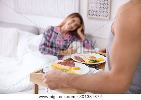 Young handsome man bringing breakfast for his beloved girlfriend in bed poster