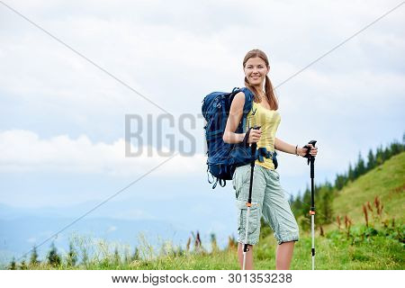 Portrait Of Young Smiling Woman Hiker Hiking Mountain Trail, Walking On Grassy Hill, Wearing Backpac