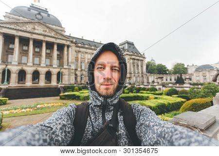 The Guy In The Jacket And Wearing A Capeshon On His Head In Bad Rainy Weather Stands Against The Bac