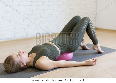 Gluteal Bridge On Small Fit Ball, Caucasian Woman Doing Pilates With Special Equipment In Fitness St