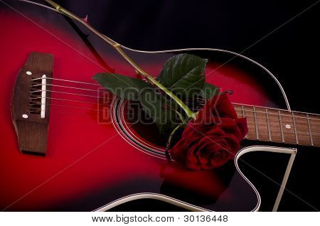 Beautiful red guitar with red rose on black background
