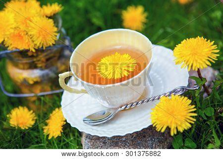 Cup of Dandelion Tea outdoors with a jar of dandelions