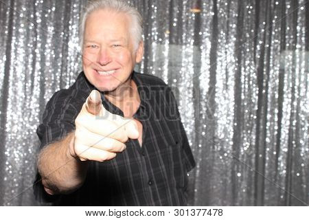Man in a Photo Booth. A handsome man smiles and points while in a photo booth. Silver sequin drape background.