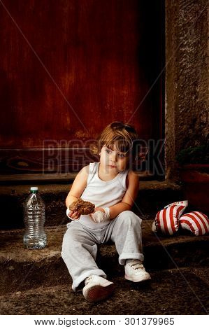Baby Boxer Sitting On The Steps With A Piece Of Bread In The Hand