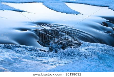 Blue Ice And The Water Making The Way And Raging From Under It