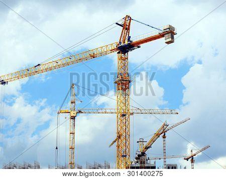 Five Construction Cranes On A Blue Cloudy Sky Background. Construction Site Background. Industrial B