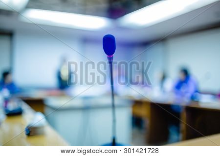 Soft Focus Of Desktop Wireless Conference Microphones With Blurry Business Group In A Meeting Room,
