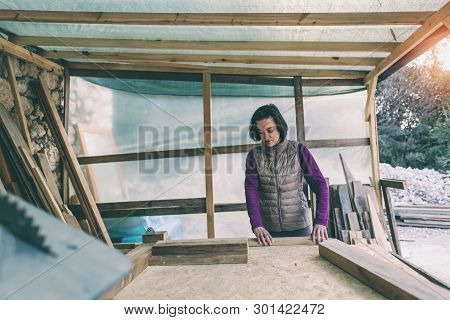 A woman works in a carpentry workshop. The girl handles the wood. Woman in the male profession. Feminism. The girl learns to work with carpentry tools. Apprentice master. poster