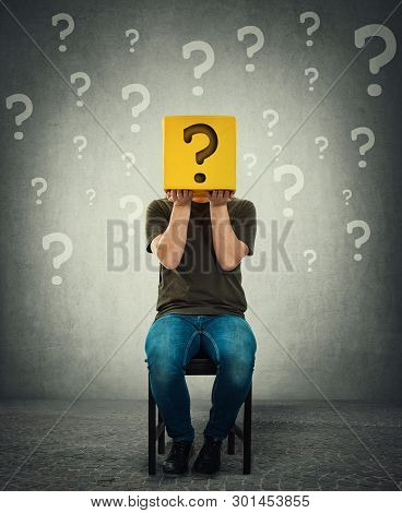 Incognito Young Man Seated On A Chair Holding A Yellow Box With Question Mark Instead Of Head. Intro