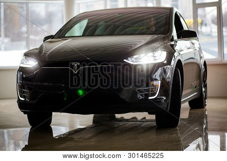 Tesla New-generation Electric Car Of Dark Brown Indoor. New Model Of Electric Vehicle By Tesla With