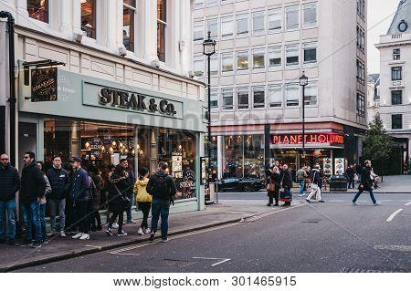 London, Uk - April 14, 2019: People Walking Past Steak & Co Restaurant On The Corner Of Haymarket, A