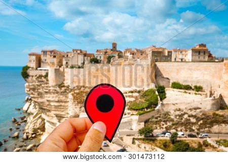 closeup of the hand of a caucasian man holding a red marker at the picturesque citadel of Bonifacio, in Corsica, France, on the top of a promontory, with the Mediterranean sea in the background