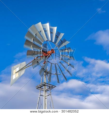 Square Shiny Steel Windpump Against A Vibrant Blue Sky With Cottony Clouds