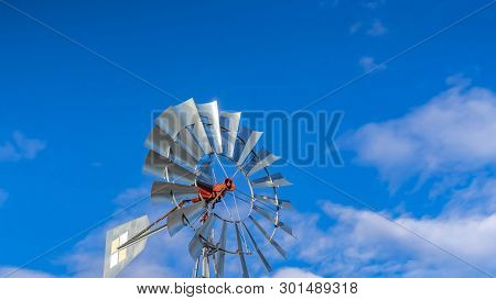 Panorama Shiny Steel Windpump Against A Vibrant Blue Sky With Cottony Clouds
