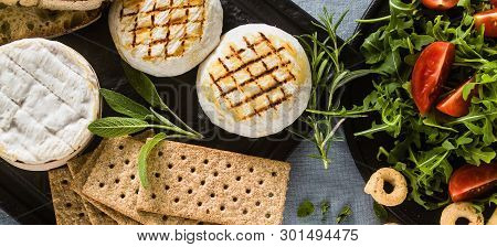 Banner Of Grilled Italian Tomino Cheese Served On A Table With White Wine, Crackers, Grissini And Ta