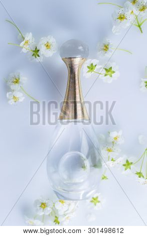 Perfume With Spring Flowers On A Gray Background
