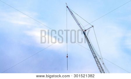 Panorama A Lifting Crane Viewed Against A Beautiful Blue Sky Filled With Cottony Clouds