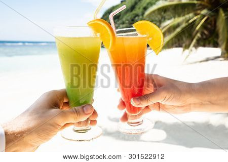 Couple's Hand Toasting The Glasses Of Cocktail At Beach