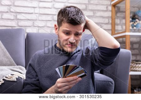 Stressed Man Looking At Too Many Credit Cards In Home