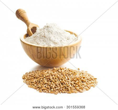 Whole grain wheat flour and wheat grains in bowl isolated on white background.