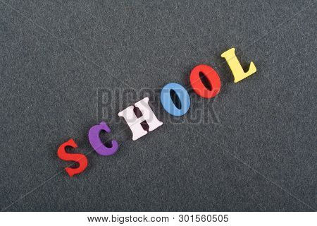 School Word On Black Board Background Composed From Colorful Abc Alphabet Block Wooden Letters, Copy