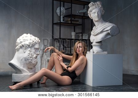 Young Woman Posing Among Ancient Greek God Apollo Bust Sculpture And Farnese Hercules Or Heracles He
