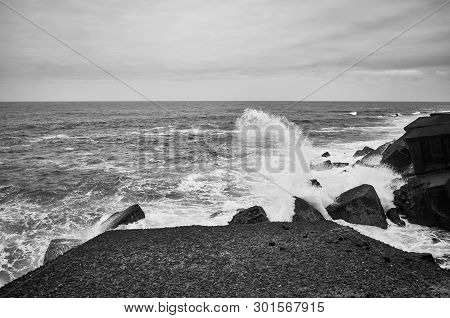 Black And White Picture Of Waves Crashing On Rocks.