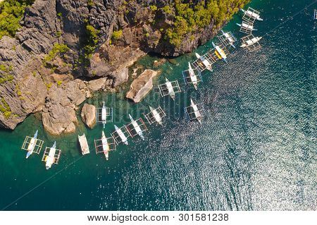 Tourist Boats Near The Rocky Shore, View From Above.the Blue Sea And The Rocky Shore Of A Tropical I