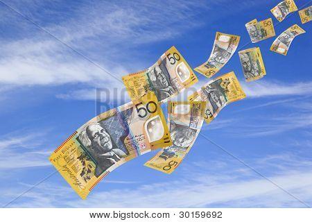 Australian fifty dollar bills falling from a blue sky.
