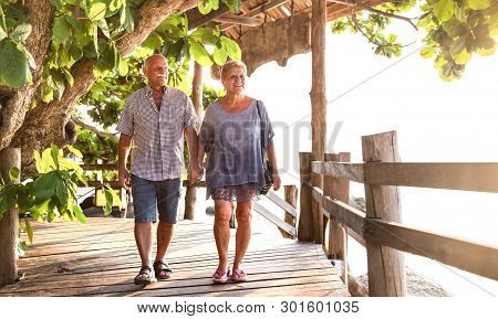 Happy Senior Couple Walking Holding Hand At Koh Phangan Beach Promenade - Active Elderly And Travel