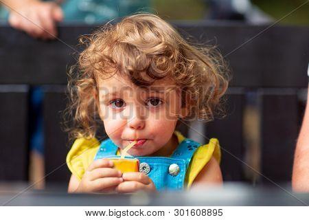 Cute Kid Girl Drinking Juice In Park